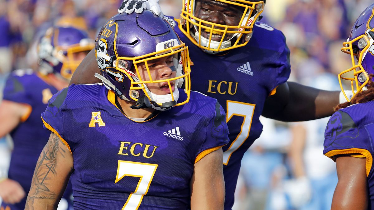 East Carolina running back Darius Pinnix (7) is congratulated by teammate D'Ante Smith (67)...