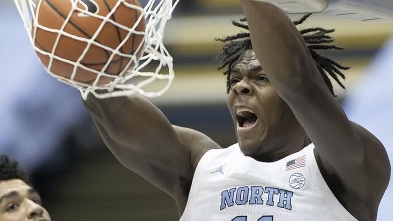 North Carolina's Day'Ron Sharpe (11) dunks next to Northeastern's Jason Strong (00) during the...