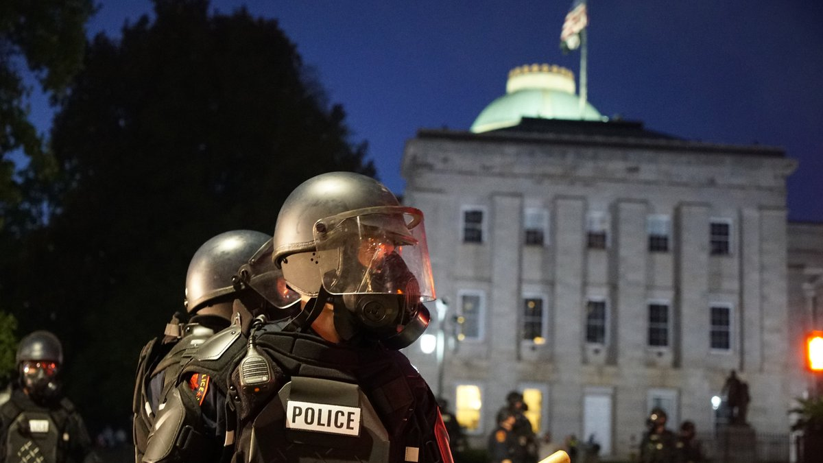 Police in riot gear protect the old state capitol building in Raleigh, N.C., on Sunday, May 31,...