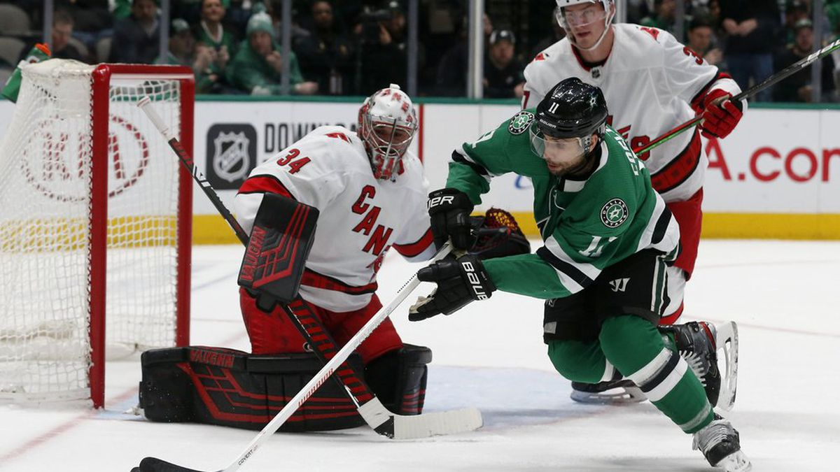 Dallas Stars center Andrew Cogliano (11) maneuvers the puck in front of Carolina Hurricanes goaltender Petr Mrazek (34) and right wing Andrei Svechnikov (37) during the first period of an NHL hockey game in Dallas, Tuesday, Feb. 11, 2020. (AP Photo/Michael Ainsworth)