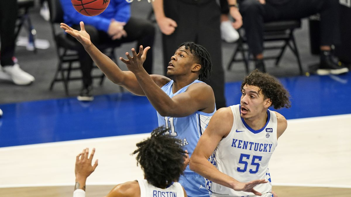 North Carolina's Day'Ron Sharpe (11) tries to get a rebound ahead of Kentucky's Lance Ware (55)...
