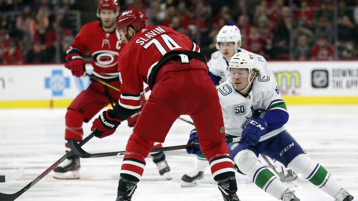 Carolina Hurricanes defenseman Jaccob Slavin (74) passes the puck while Vancouver Canucks right wing Brock Boeser (6) defends during the first period of an NHL hockey game in Raleigh, N.C., Sunday, Feb. 2, 2020. (AP Photo/Gerry Broome)