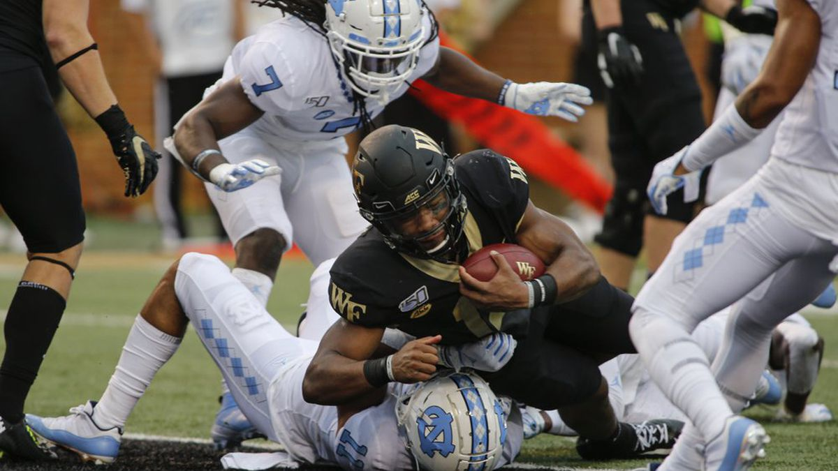 Wake Forest quarterback Jamie Newman (12) rushes for a touchdown over North Carolina defensive back Myles Wolfolk (11) during the first half of an NCAA college football game in Winston-Salem, N.C., Friday, Sept. 13, 2019. (AP Photo/Nell Redmond)