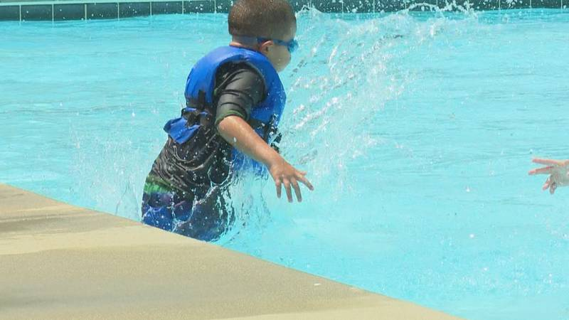 A child jumps in the water for a swim lesson at the community pool in Greenville on Thursday.