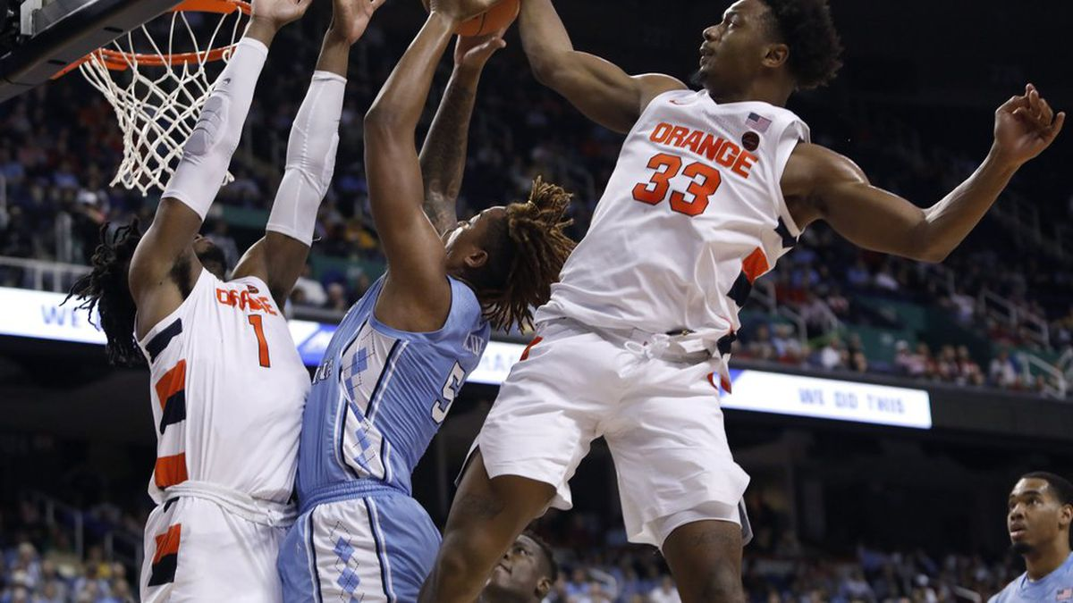 Syracuse forward Elijah Hughes (33) and forward Quincy Guerrier (1) block North Carolina forward Armando Bacot (5) during the first half of an NCAA college basketball game at the Atlantic Coast Conference tournament in Greensboro, N.C., Wednesday, March 11, 2020. (AP Photo/Ben McKeown)