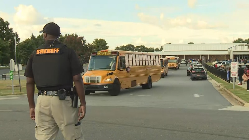 Buses leave Parkland High School after a shooting near campus Friday afternoon.