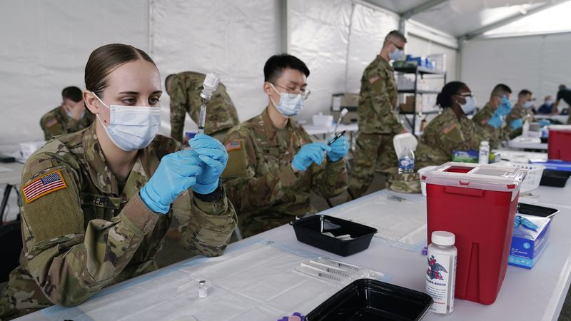 FILE - In this March 9, 2021, file photo, Army health specialists fill syringes with the Pfizer...