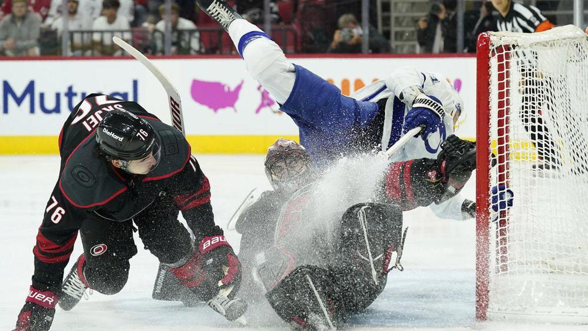 Tampa Bay Lightning center Anthony Cirelli, top right, falls over Carolina Hurricanes...