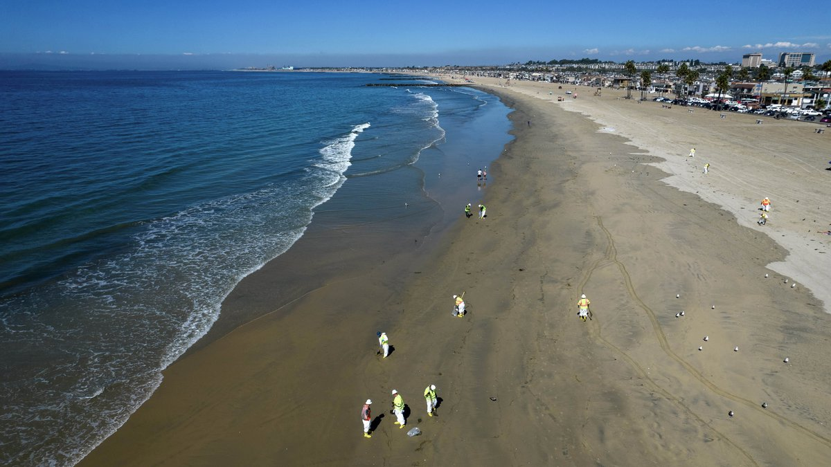 Workers clean oil from the sand south of the pier in Newport Beach, Calif., Tuesday, Oct. 5,...