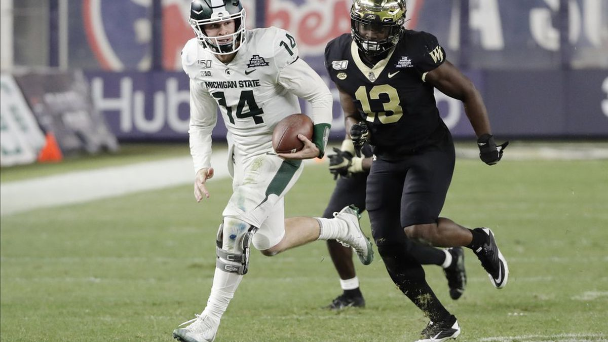 Michigan State quarterback Brian Lewerke (14) runs away from Wake Forest defensive lineman Manny Walker (13) during the second half of the Pinstripe Bowl NCAA college football game Friday, Dec. 27, 2019, in New York. (AP Photo/Frank Franklin II)