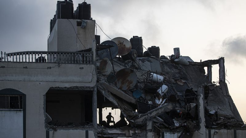 A Palestinian searches for survivors under the rubble of a destroyed rooftop of a residential...