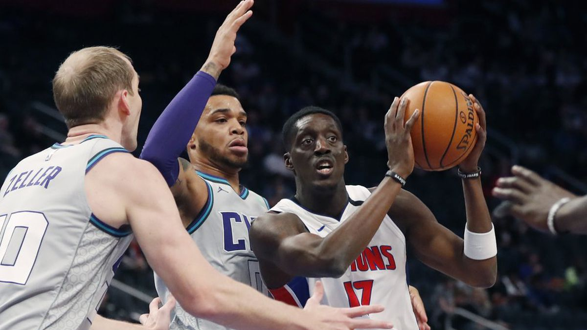Detroit Pistons forward Tony Snell (17) passes as Charlotte Hornets forward Miles Bridges (0) and center Cody Zeller (40) defend during the first half of an NBA basketball game, Monday, Feb. 10, 2020, in Detroit. (AP Photo/Carlos Osorio)
