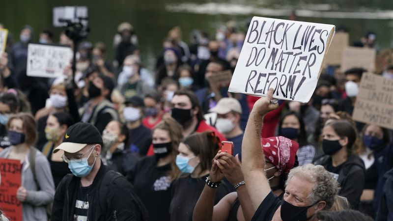 FILE - In this Sept. 29, 2020, file photo, a man holds a sign during a protest, in Cleveland....