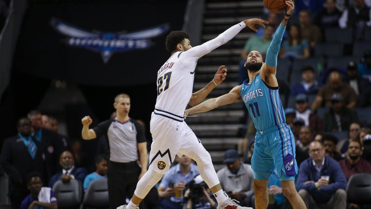 Charlotte Hornets forward Cody Martin, right, breaks up a pass by Denver Nuggets guard Jamal...