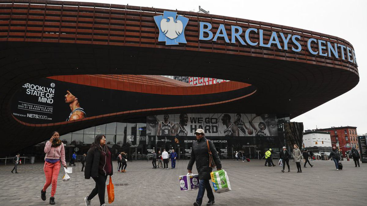 FILE - In this March 12, 2020, file photo, pedestrians walk past the Barclays Center, which is home to the Brooklyn Nets, in the Brooklyn borough of New York. The Nets announced on Tuesday, March 17, 2020, that four players have tested positive for the new coronavirus, bringing the total to seven known players in the NBA. (AP Photo/John Minchillo, File)