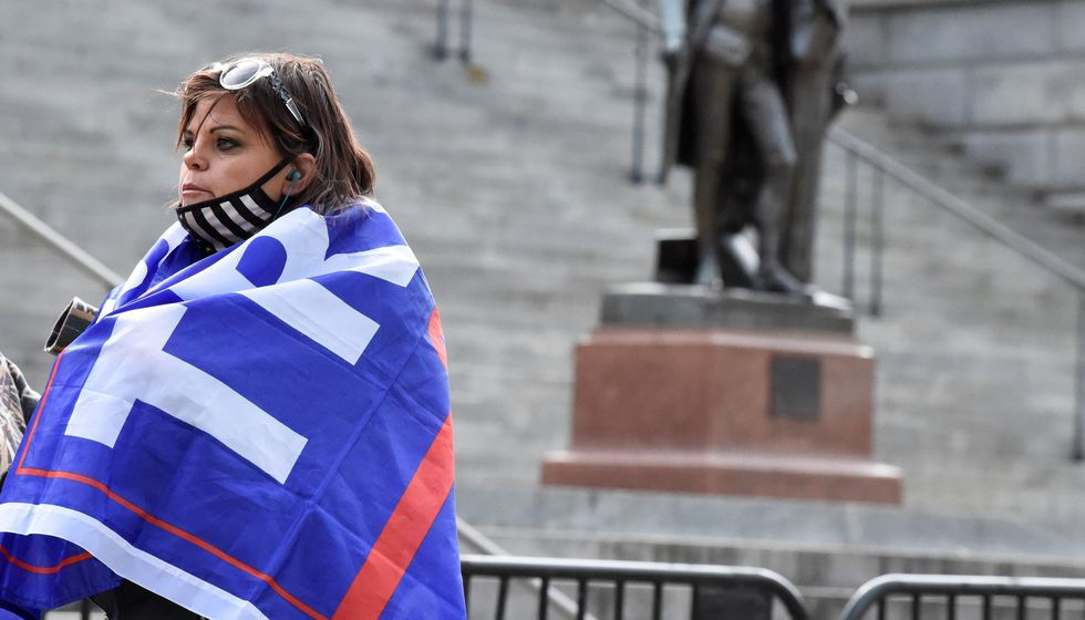 A woman with a Trump flag draped around her shoulders stands near a blocked-off statue of...