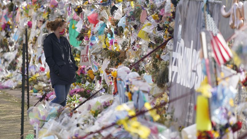 Tributes hang on the temporary fence surrounding the parking lot in front of a King Soopers...