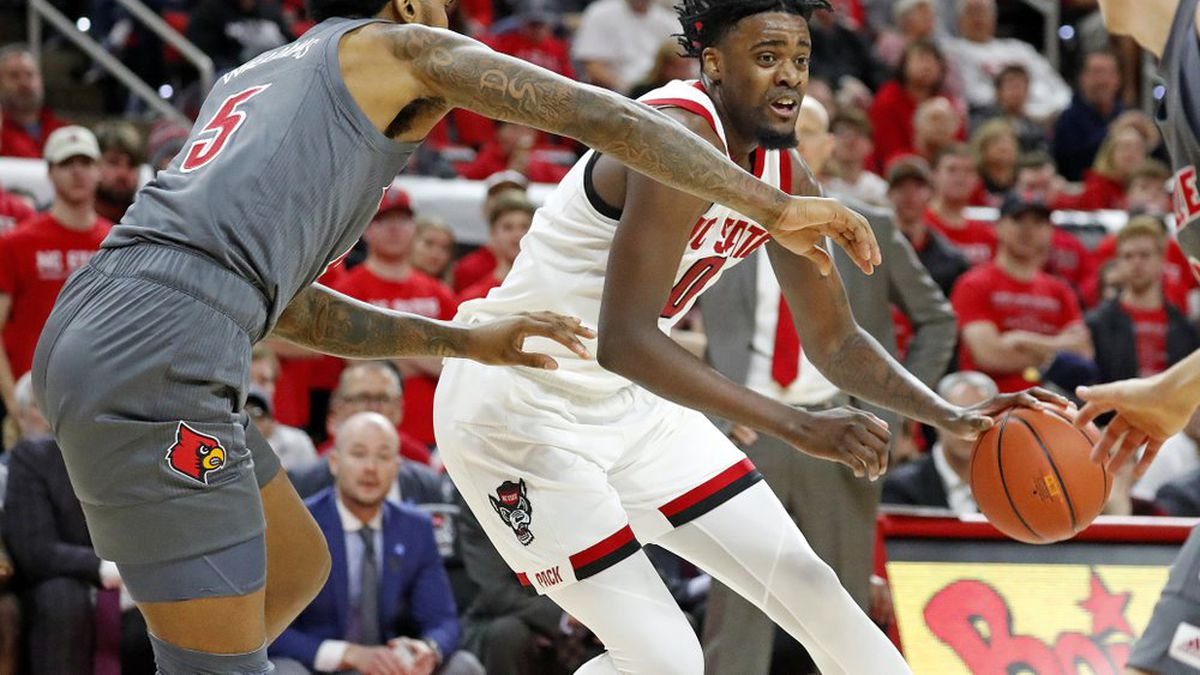 North Carolina State's DJ Funderburk (0) drives the ball as Louisville's Malik Williams (5) defends during the first half of an NCAA college basketball game in Raleigh, N.C., Saturday, Feb. 1, 2020. (AP Photo/Karl B DeBlaker)