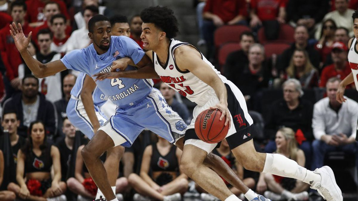 Louisville forward Jordan Nwora (33) drives to the basket as he's defended by North Carolina guard Brandon Robinson (4) during an NCAA college basketball game Saturday, Feb. 22, 2020, in Louisville, Ky. (AP Photo/Wade Payne)