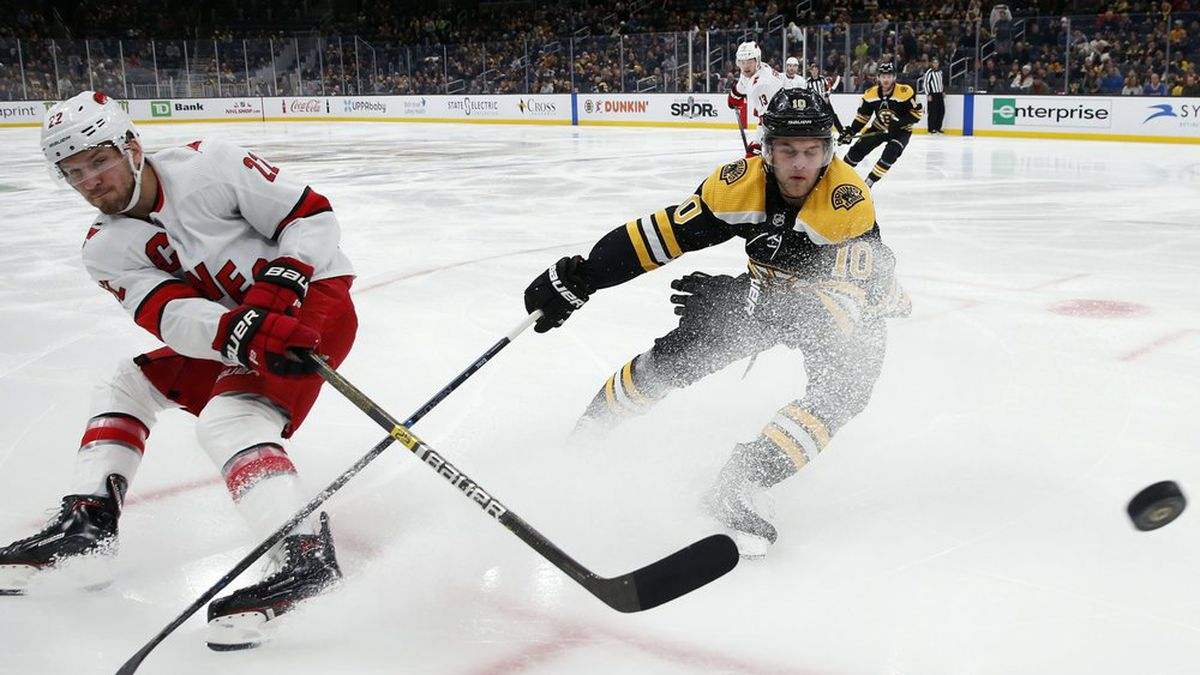 Carolina Hurricanes' Brett Pesce (22) sends the puck past Boston Bruins' Anders Bjork (10) during the first period of an NHL hockey game in Boston, Tuesday, Dec. 3, 2019. (AP Photo/Michael Dwyer)