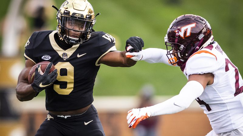 Wake Forest sophomore running back Kenneth Walker III (9) breaks a tackle from Virginia Tech...