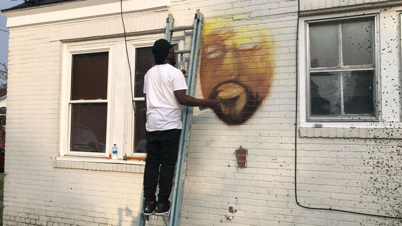 Tattoo artist painting a mural of Andrew Brown on Brown's house.