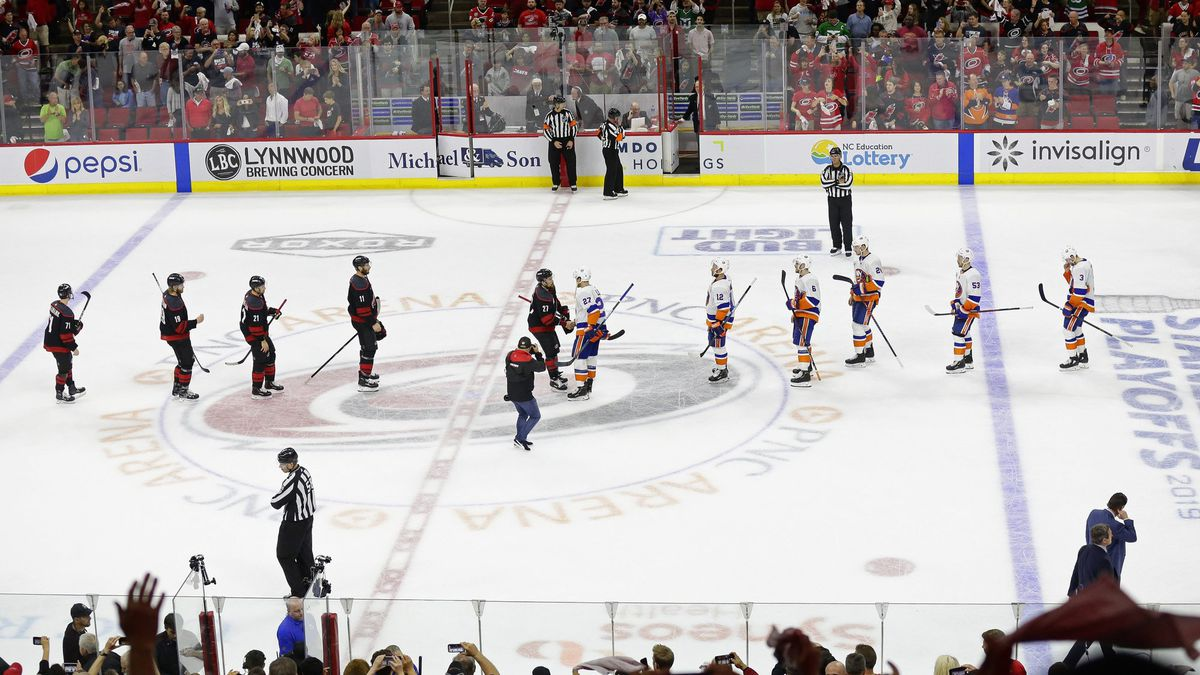 Carolina Hurricanes players and New York Islanders players shake hands following Carolina's win in Game 4 of an NHL hockey second-round playoff series in Raleigh, N.C., Friday, May 3, 2019. (AP Photo/Gerry Broome)