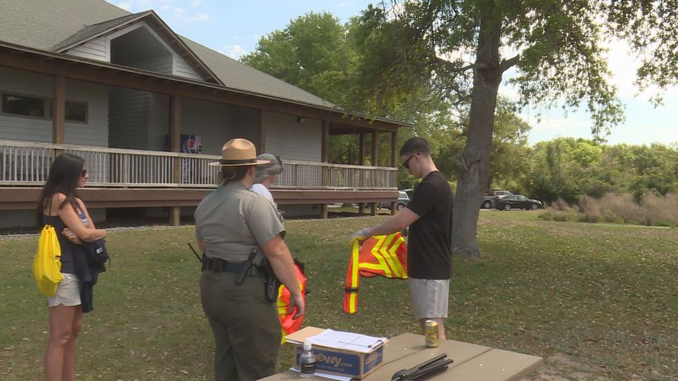 Park Ranger passing out safety vests to volunteers for Hammock Beach State Park Cleanup.