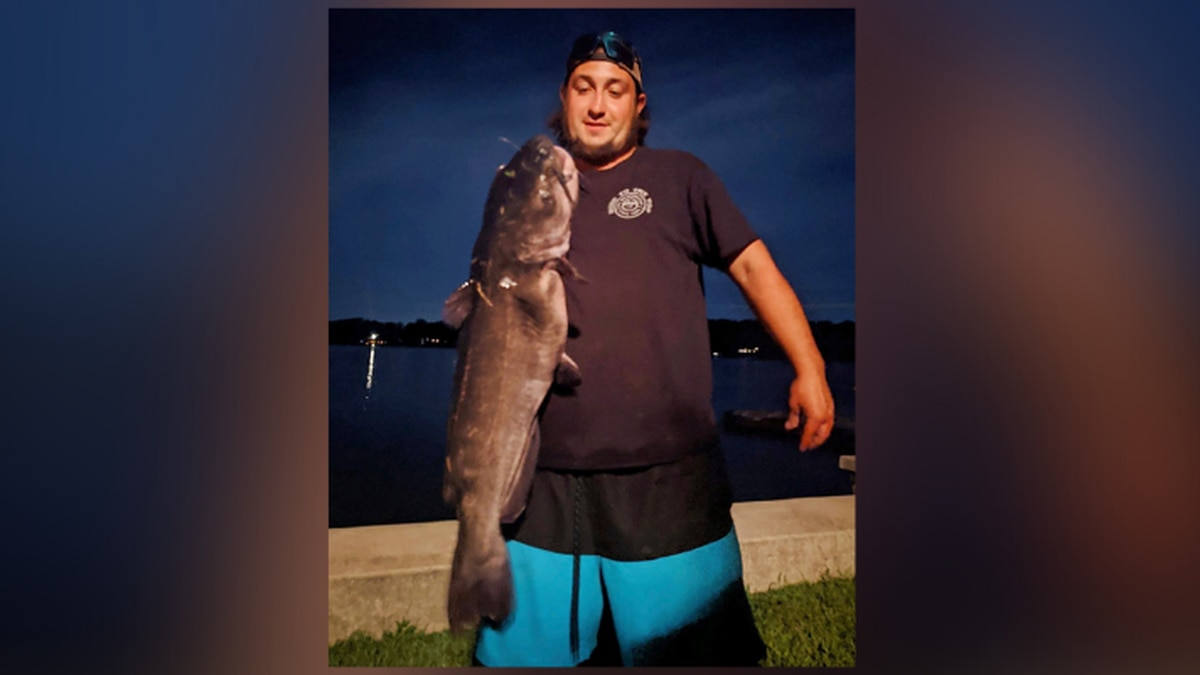 Ben Tomkunas holds a catfish he caught in Coventry, Conn., on Aug. 21, 2021, that has smashed a...