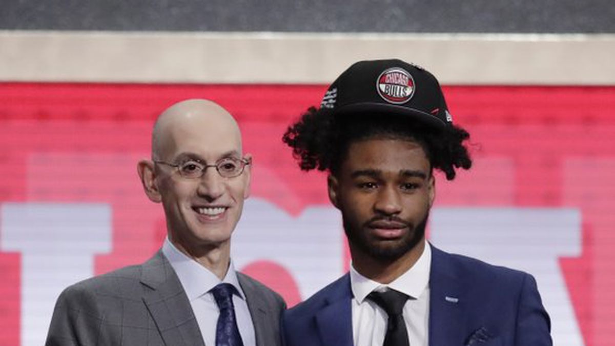 NBA Commissioner Adam Silver, left, poses for photographs with North Carolina's Coby White after the Chicago Bulls selected White as the seventh overall pick in the NBA basketball draft Thursday, June 20, 2019, in New York. (AP Photo/Julio Cortez)
