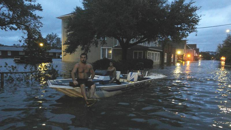 Two men use a boat to explore a street flooded by Hurricane Irene Saturday, Aug. 27, 2011 in...