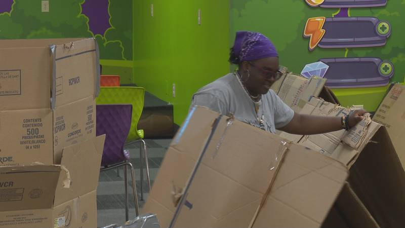 Kendra Dixon, 16, fixes the cardboard tent she'll sleep in for a night to raise awareness about...