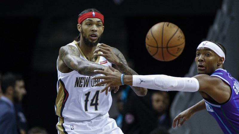 New Orleans Pelicans forward Brandon Ingram, left, passes around Charlotte Hornets guard...