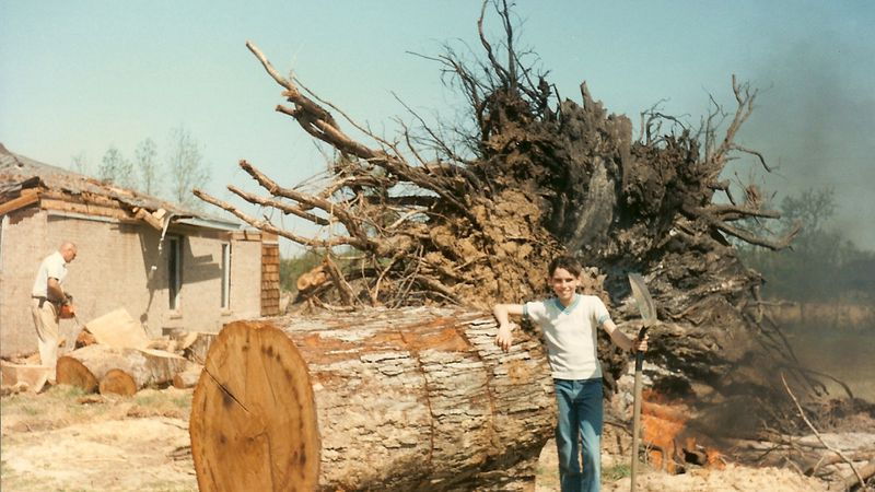 Norman Bryson stands next to the trunk of a tree that was struck by lightning and fell on his...