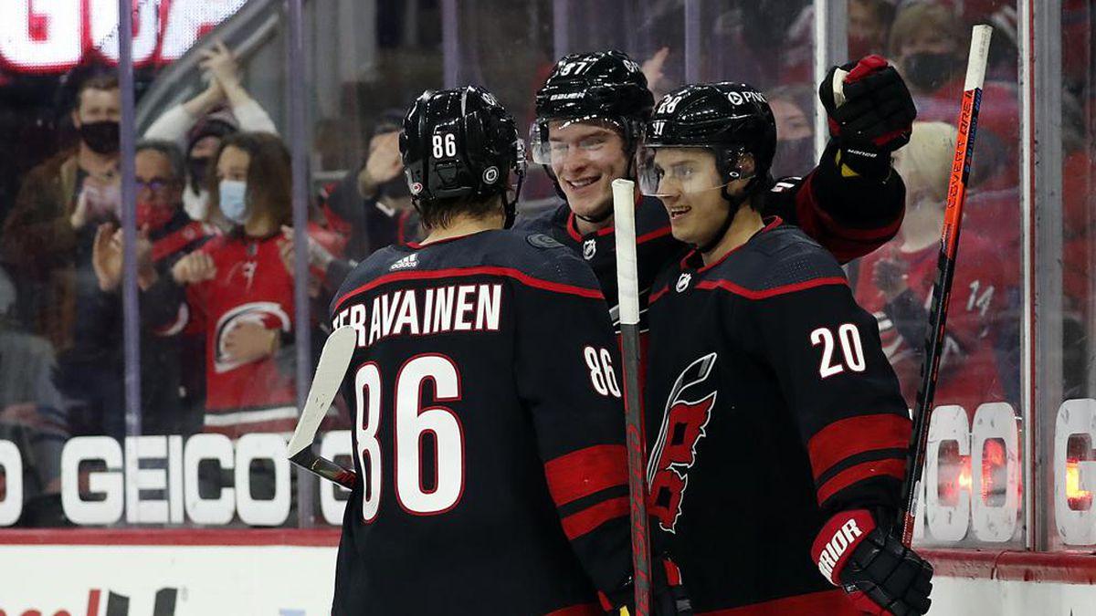 Carolina Hurricanes' Teuvo Teravainen (86) and Andrei Svechnikov (37) congratulate teammate...