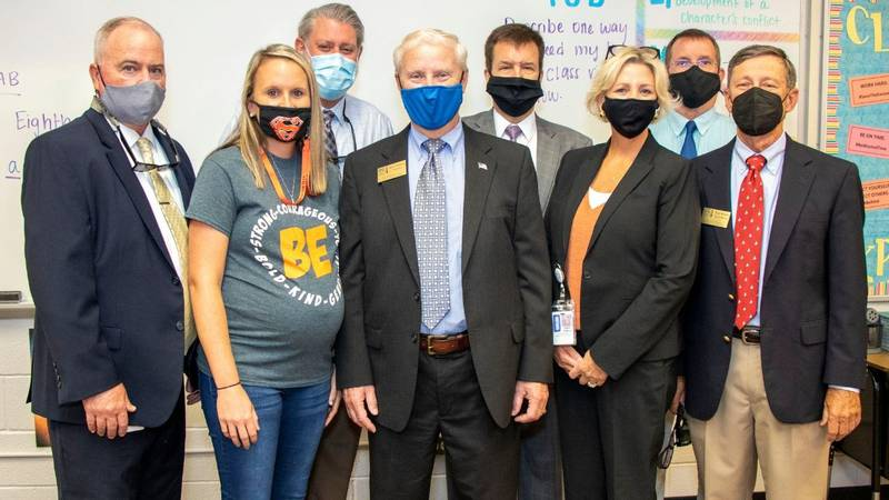 Chelsea D'Zurilla, joined by Superintendent Dr. Barry Collins and a group of district leaders...