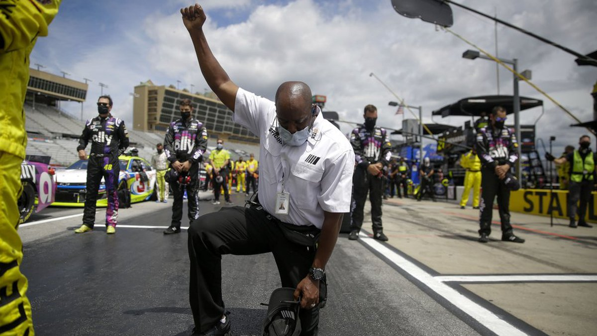 A NASCAR official kneels during the national anthem before a NASCAR Cup Series auto race at...