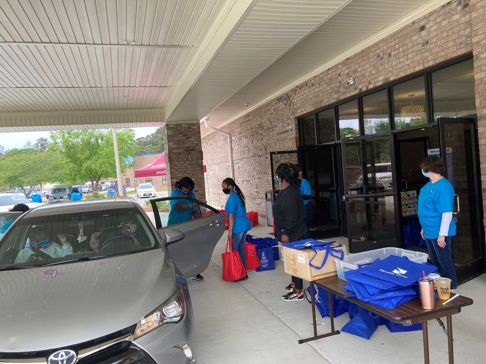 Volunteers handing out care packages at the NC MedAssist free pharmacy giveaway.