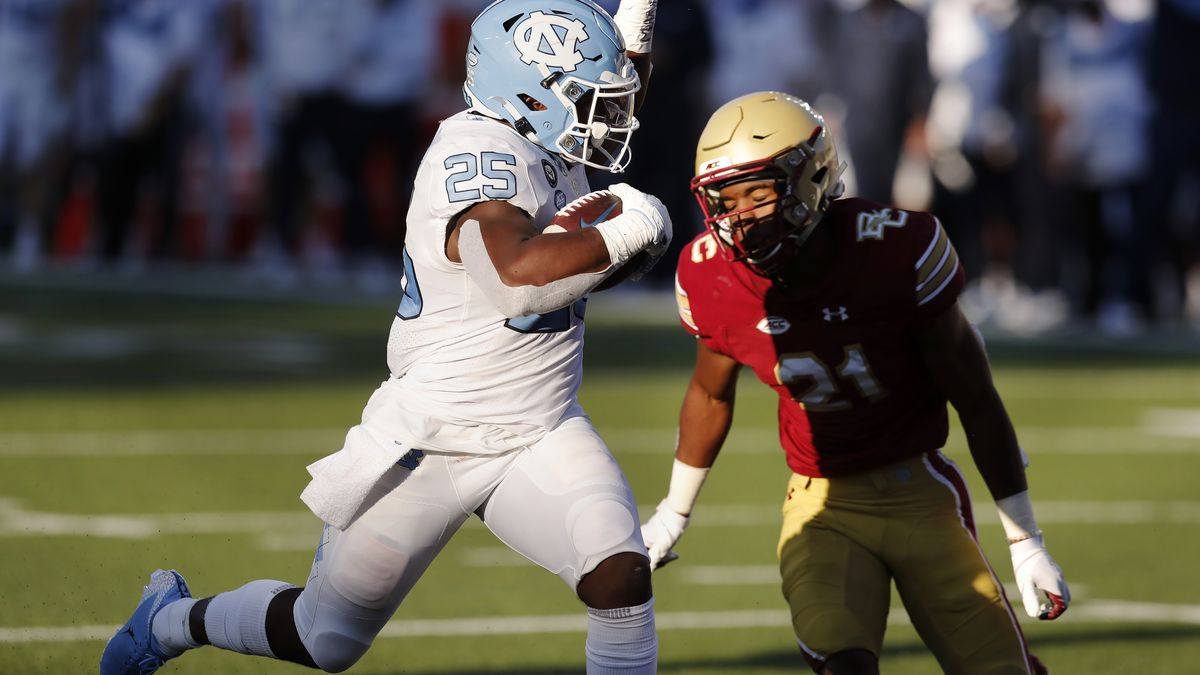 North Carolina running back Javonte Williams (25) runs for a touchdown against Boston College defensive back Josh DeBerry (21) during the first half of an NCAA college football game, Saturday, Oct. 3, 2020, in Boston. (AP Photo/Michael Dwyer)