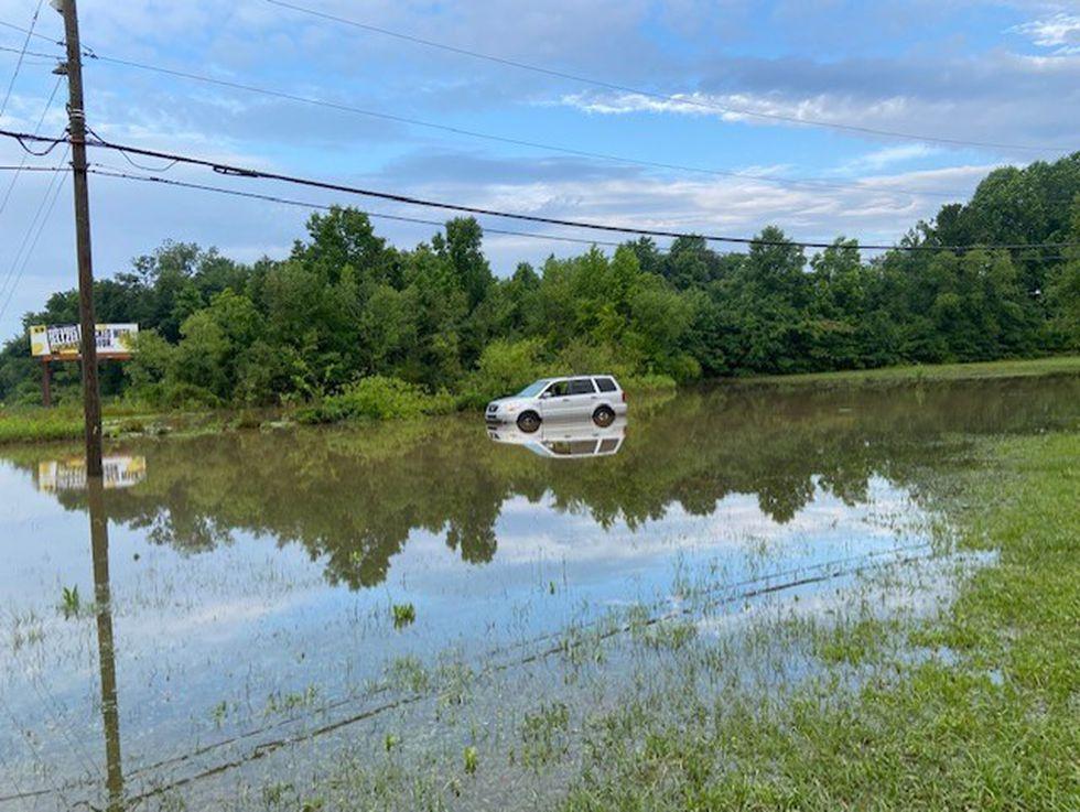 A car is stuck in standing water on Evans Street near Arlington Boulevard.