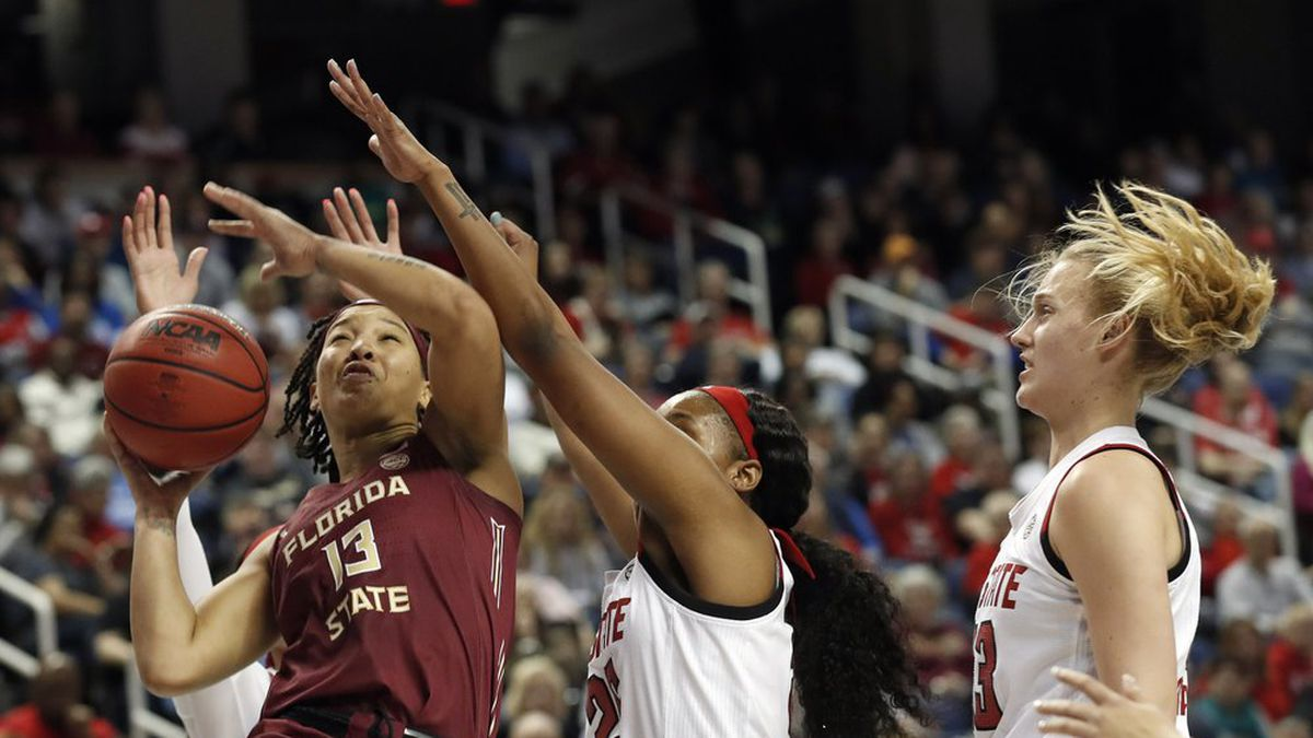 Florida State guard Nausia Woolfolk (13) drives to the basket while North Carolina State forward Kayla Jones and center Elissa Cunane, right, defend during the first half of an NCAA college basketball championship game at the Atlantic Coast Conference women's tournament in Greensboro, N.C., Sunday, March 8, 2020. (AP Photo/Gerry Broome)