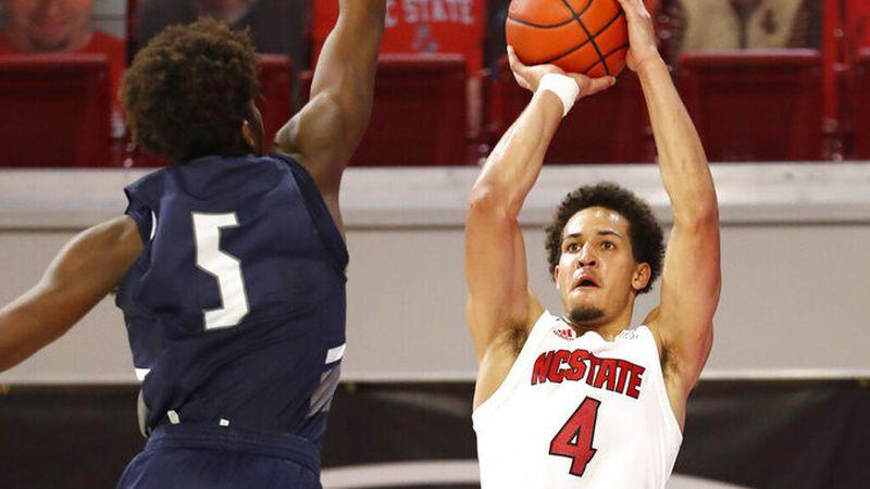 North Carolina State's Jericole Hellems (4) shoots as North Florida's Dorian James (5) defends...